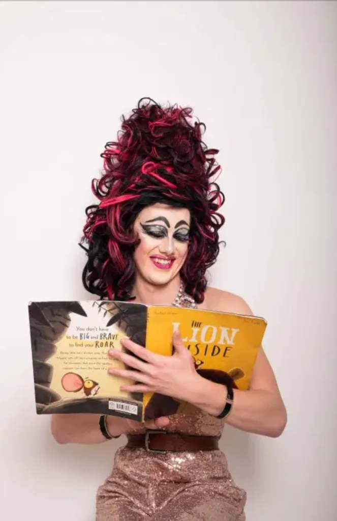 A white drag queen with dramatic eye makeup, wearing a large wig in shades of dark red, purple and pink, and reading from a story book.