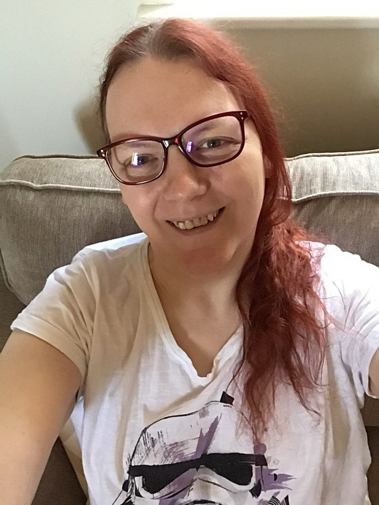 A smiling white woman with long red hair, wearing glasses with dark red frames, and smiling at the camera.