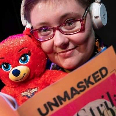 Close-up of a short-haired white woman wearing glasses and white headphones, holding a red teddy bear alongside her head